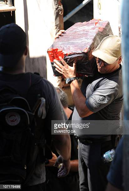 A policema carries a block of marijuana seized during the raid in the Morro do Alemao shantytown on November 28 2010 in Rio de Janeiro Brazil After...