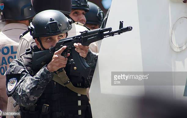 """Policeman aims his Kalashnikov assault rifle as security forces come under fire in """"La Vega"""" low income neighborhood during a demonstration by local..."""