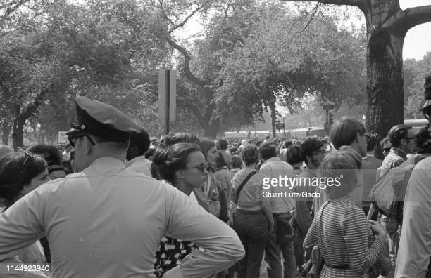 Policeman and a crowd of protestors, from the back, standing in a tree-covered area during the Kent State/Cambodia Incursion Protest, Washington,...