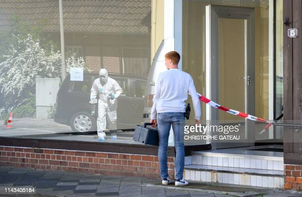 A policeman and a forensic expert arrive to secure evidences on May 13 2019 in a cordoned off house in Wittingen northern Germany where two bodies...