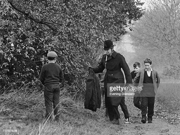 A policeman and a group of boys near the spot on the Thames towpath where the body of murder victim Gwynneth Rees was discovered November 1963 Rees...