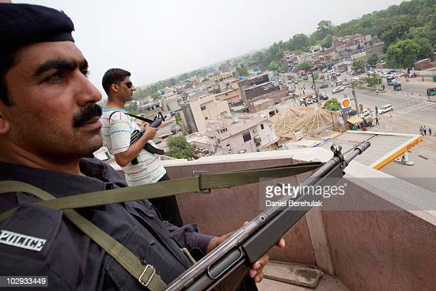 A policeman and a private security guard keep watch from the turret of the Garhi Shahu mosque as members of the persecuted Ahmadiyya community gather...