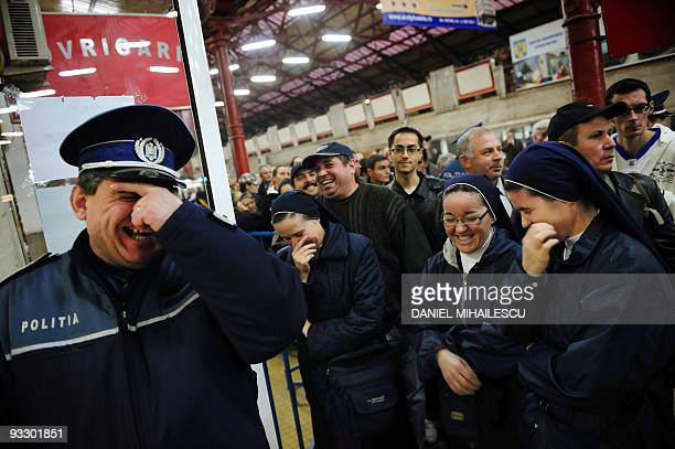 A policeman and catholic nuns laughs togheter at the entrance of a special polling station in the Gara de Nord in Bucharest on November 22 2009 Polls...