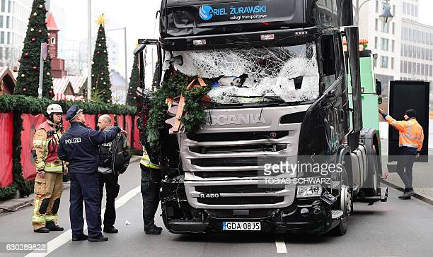 A policeman and firemen stand next to a truck on December 20 2016 at the scene where it crashed into a Christmas market near the...
