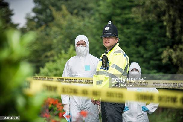Policeman and forensic scientists at crime scene with police tape in foreground