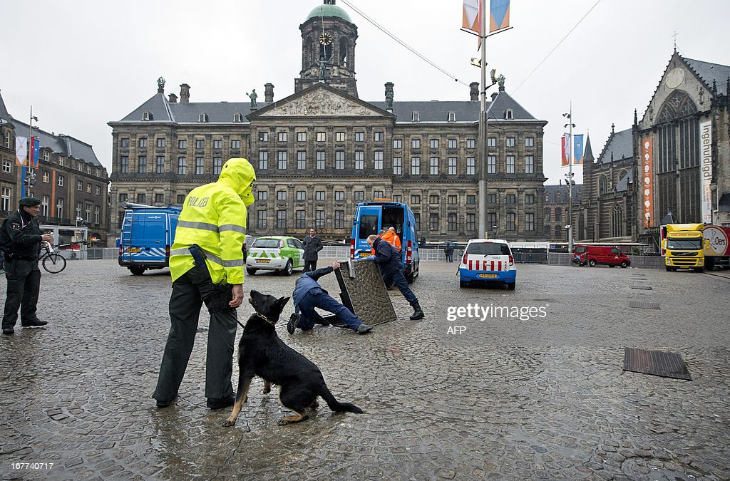 A policeman and his service dog are looking for potential explosives on Dam Square in Amsterdam, The Netherlands, on April 29, 2013, on the eve of the abdication of Dutch Queen Beatrix and the investiture of Prince Willem Alexander as King on April 30. netherlands out