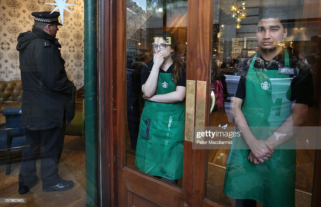 A policeman and members of staff watch from inside a Starbucks coffe shop as UK UNCUT supporters protest outside on December 8, 2012 in London, England. UK UNCUT are holding a day of protests at various Starbucks throughout the United Kingdom after the coffe chain were revealed to be paying almost no corporation tax.