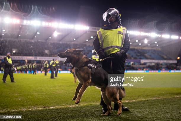 A policeman and police dog are seen on the pitch after the FA Cup Fourth Round match between Millwall and Everton at The Den on January 26 2019 in...