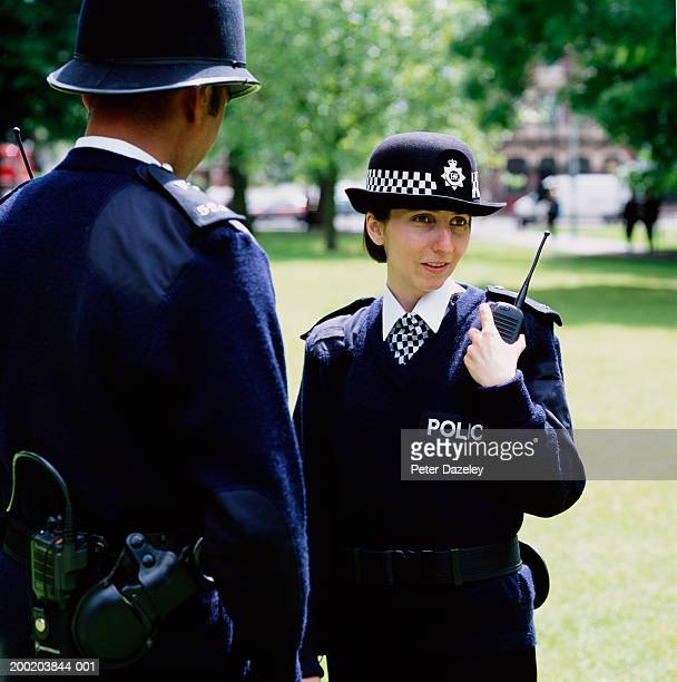 Policeman and woman outdoors, policewoman using radio