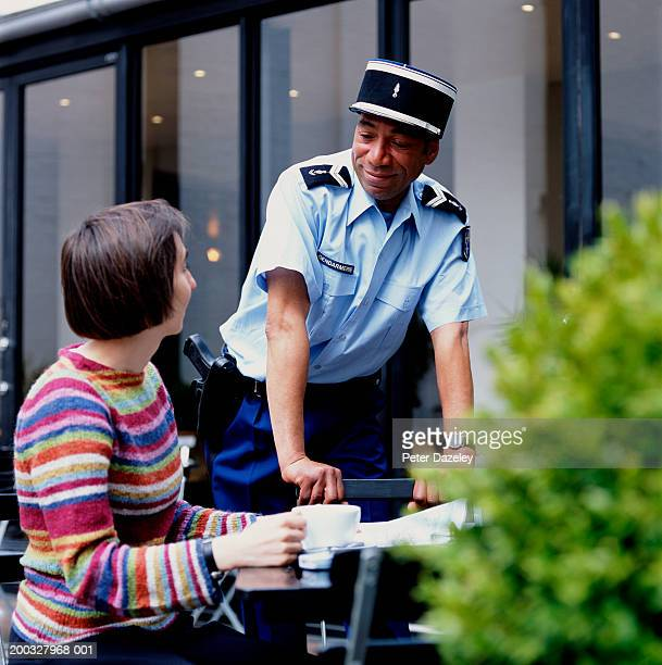 policeman and woman talking by outdoor cafe - french culture stock pictures, royalty-free photos & images