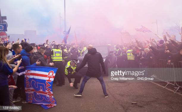 Policeman appears to lose his footing as Rangers fans greet the arrival of their players and manager pre match during a Scottish Premiership match...