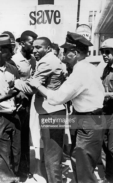 A policeman applies an arm lock on comedian Dick Gregory after he left the Leflore County Court House to help Negroes register to vote Greenwood...