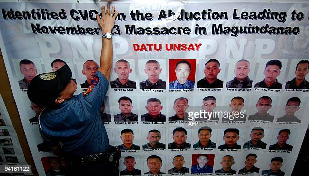 A policeman arranges the tarpaulin showing pictures of Philippine Civilian Volunteer Officers members of a group assissting the police force in...