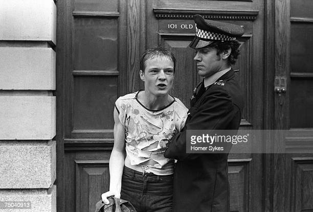 A policeman arresting a punk wearing a fashionable ripped tshirt in Sloane Square Chelsea 1977