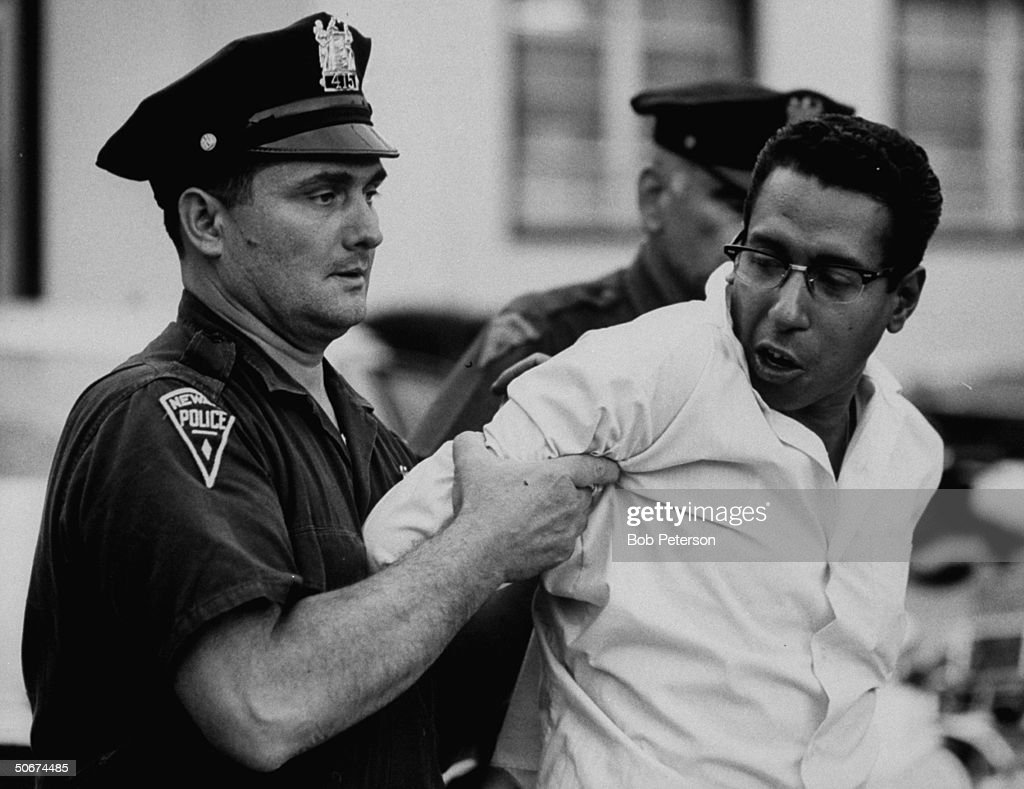 Policeman arresting a suspect during riots.