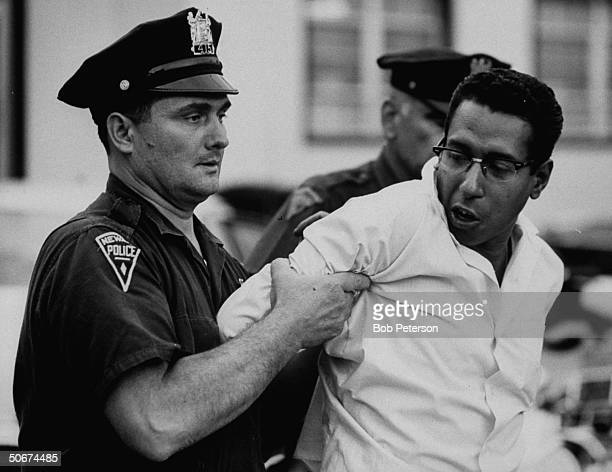 Policeman arresting a suspect during riots