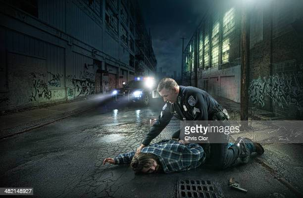 policeman arresting man on city street - arrest stock pictures, royalty-free photos & images