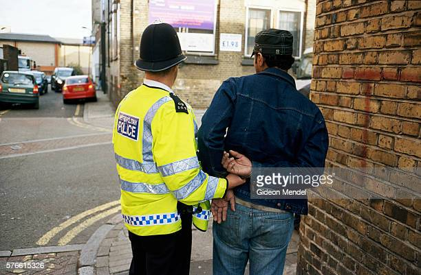 policeman arresting suspected illegal immigrant - police force stock pictures, royalty-free photos & images