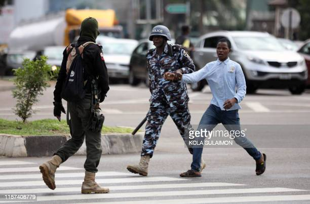 Policeman arrests a man for questioning during a violent protest of Shiite Muslims demanding the release of their detained leader Ibrahim Zakzaky, on...