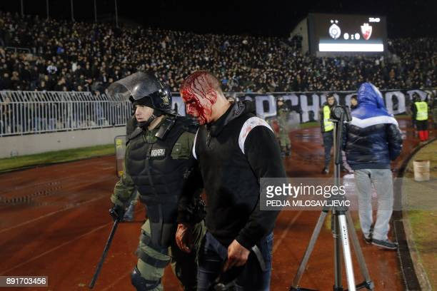 A policeman arrests a Partizan Belgrade's hooligan after clashes between two groups of Partizan Belgrade's supporters during the Serbian Superleague...