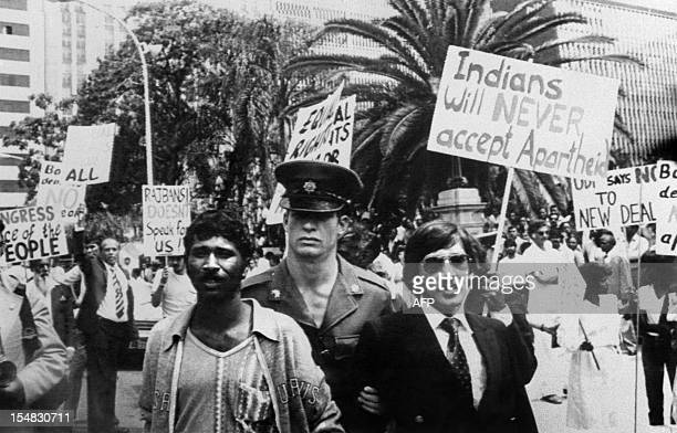 A policeman arrests two indian men of South Africa on November 14 1983 during a demonstration against apartheid outside Durban city Hall