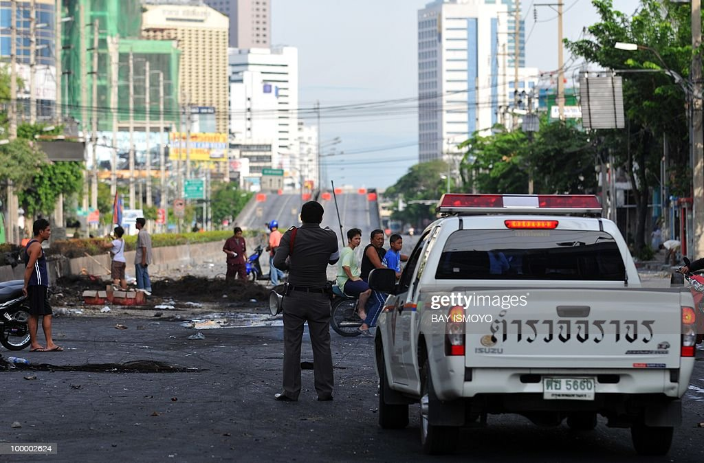 A policeman asks curious people to leave the scene where clashes between protesters and security raged in the previous days on Rama IV boulevard in downtown Bangkok on May 20, 2010. Plumes of smoke hung overhead as Bangkok emerged from an curfew aimed at quelling mayhem unleashed by enraged anti-government protesters targeted in an army offensive on May 2010.