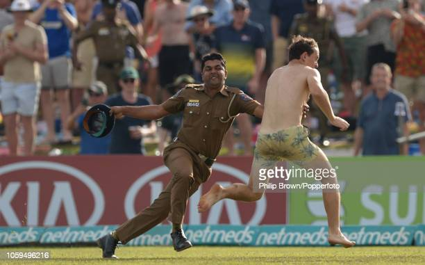 Policeman attempts to stop a spectator running on the field after the 1st Cricket Test Match between Sri Lanka and England at the Galle Cricket...