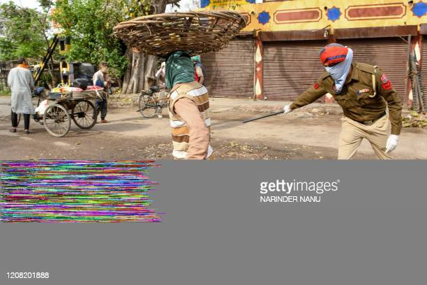Policeman beats a man with a stick alongside a street during the first day of a 21-day government-imposed nationwide lockdown as a preventive measure...