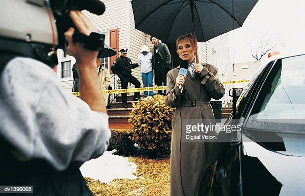 Policeman Being Interviewed by the Media on a Driveway at a Crime Scene