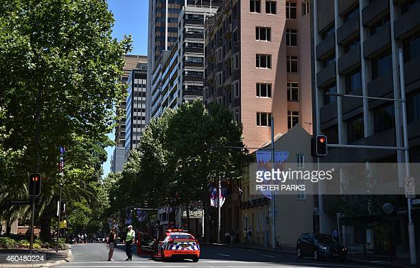 A policeman blocks a street in the central business district of Sydney on December 15 2014 A gunman was holding terrified hostages inside a Sydney...