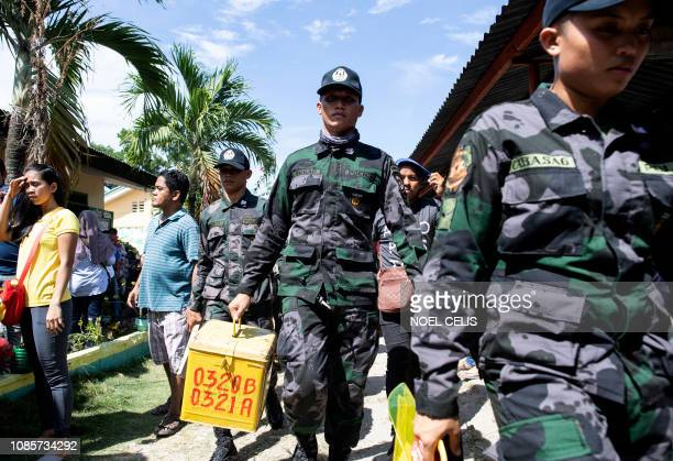 A policeman carries a ballot box at a voting precinct in Cotabato on the southern Philippine island of Mindanao on January 21 during a vote on giving...