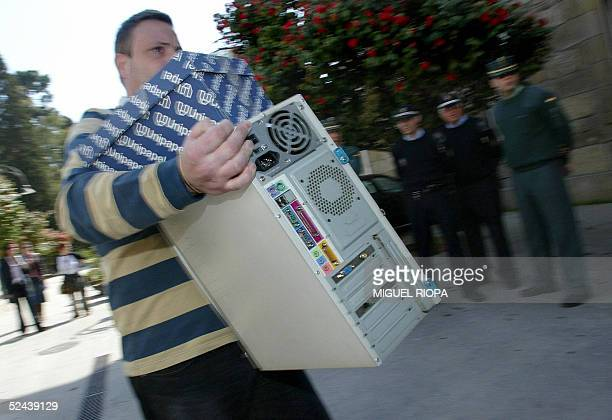 A policeman carries a computer confiscated during an international Internet child pornography sweep in Caldas de Reyes northwestern Spain 17 March...