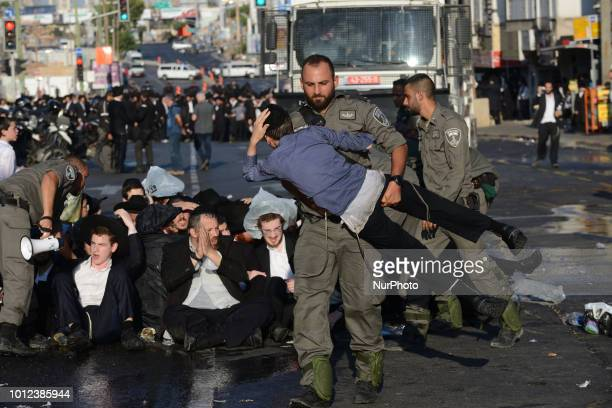 A policeman carries a protester child as Ultra orthodox Jews clash with police during a protest against the arrest of ultra orthodox men who failed...