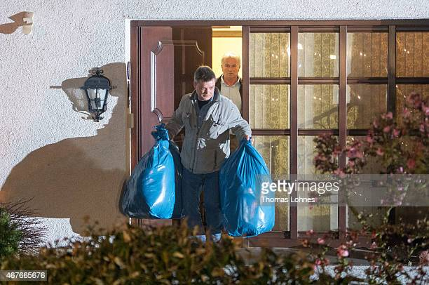 A policeman carries bags out of the residence of the parents of Andreas Lubitz copilot on Germanwings flight 4U9525 on March 26 2015 in Montabaur...