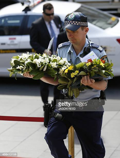 A policeman carries floral tributes into a state memorial service for former Australian prime minister Gough Whitlam at the Sydney Town Hall on...
