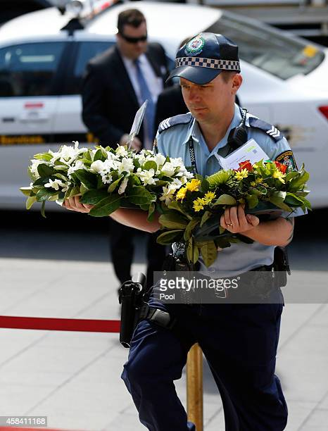 A policeman carries floral tributes to the state memorial service for former Australian Prime Minister Gough Whitlam at Sydney Town Hall on November...