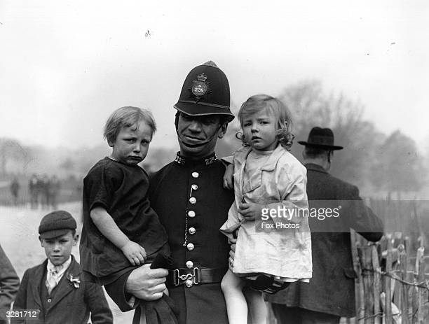 A policeman carrying two children on Hampstead Heath London