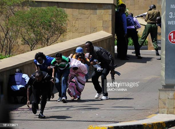 A policeman carry's a baby to safety after masked gunmen stormed an upmarket mall and sprayed gunfire on shoppers and staff killing at least six on...
