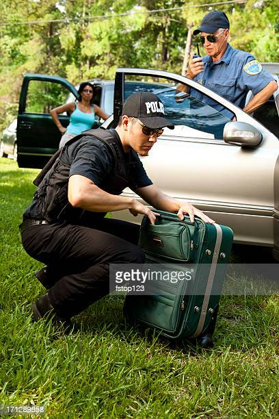 Policeman checking woman's luggage during vehicle search