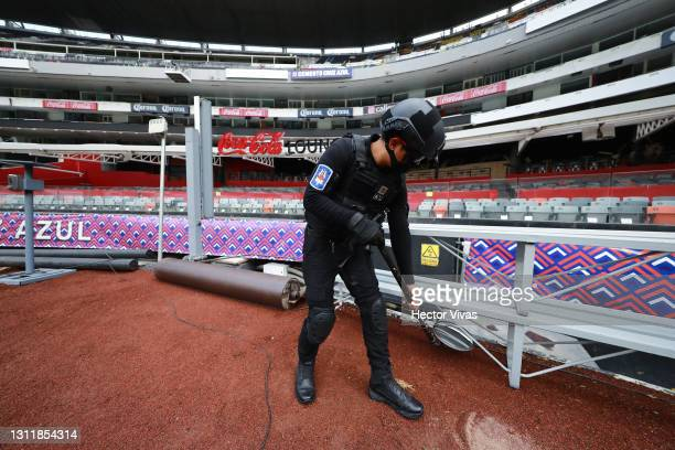 Policeman checks a bench prior the 14th round match between Cruz Azul and Chivas as part of the Torneo Guard1anes 2021 Liga MX at Azteca Stadium on...