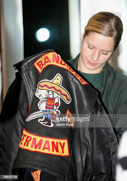 Policeman checks a jacket of a member of the biker group 'Bandidos' outside the district court on January 9,2008 in Muenster, Germany. The two biker...