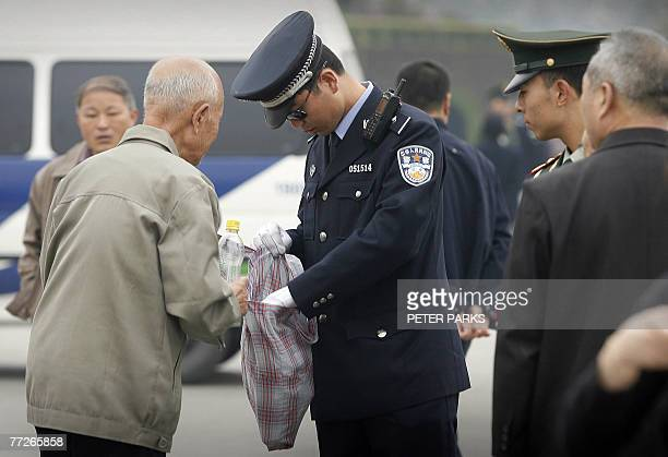 Policeman checks a man's bag at Tiananmen Square in Beijing, 11 October 2007, as China's ruling Communist Party has intensified a crackdown on...