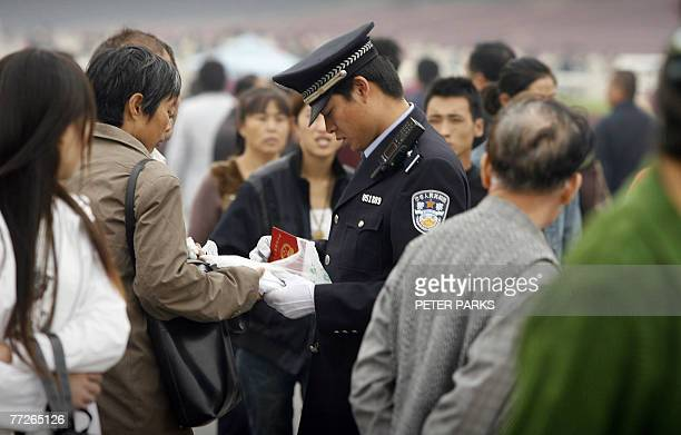 Policeman checks a man's identity at Tiananmen Gate in Beijing, 11 October 2007, as China's ruling Communist Party has intensified a crackdown on...