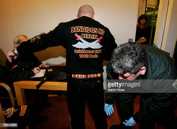 Policeman checks a member of the biker group 'Bandidos' outside the district court on January 92008 in Muenster Germany The two biker groups at...