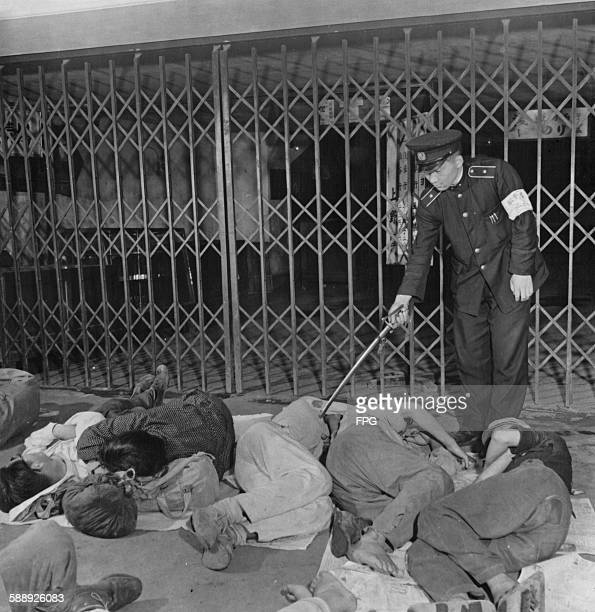 A policeman checks on the homeless people sleeping on the ground in Ueno Station Tokyo Japan circa 1947