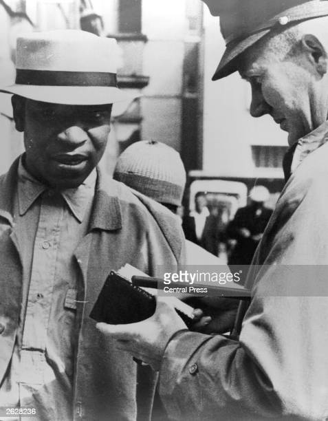 A policeman checks the identity card of a black citizen Enforcement of the Pass Laws controlled the movement and employment of blacks