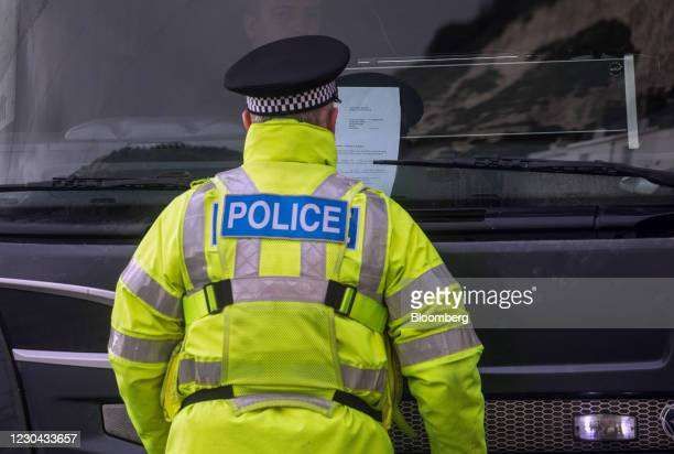 Policeman checks the paperwork in the front window of a truck at the entrance to the Port of Dover Ltd. In Dover, U.K., on Tuesday, Jan. 5, 2021. The...