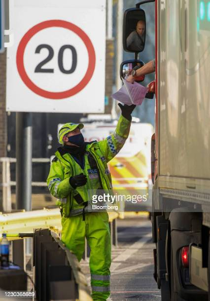 Policeman checks the paperwork of a truck driver at the entrance to the Port of Dover Ltd. In Dover, U.K., on Thursday, Dec. 31, 2020. On the day the...