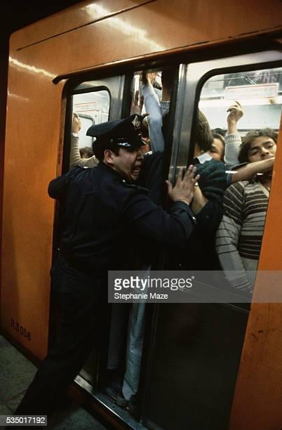 Policeman Closing Doors of Jammed Subway Car