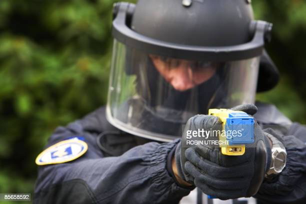 A policeman conducts a demonstration of a Taser electroshock weapon in Soesterberg on March 27 2009 Special teams of police and Royal Marshals will...